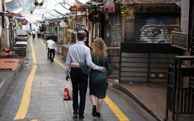 Photo d'illustration : Un couple marche à Jérusalem, au marché Mahane Yehuda, pendant le confinement entraîné par le coronavirus, le 25 septembre 2020. (Crédit : Nati Shohat/Flash90)