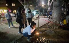 Une femme allume des bougies à la mémoire des femmes assassinées lors de violences domestiques, sur un mémorial situé sur le boulevard Rothschild, à Tel Aviv, à l'occasion de la Journée internationale de la violence contre les femmes, le 24 novembre 2020. (Miriam Alster/FLASH90)