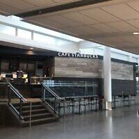 Des membres de l'équipage d'un avion passent devant un café Starbucks vide à l'aéroport international  Pierre Elliott Trudeau à Montréal, le 17 mars 2020. (Crédit :  JOCELYNE ZABLIT/AFP via Getty Images)