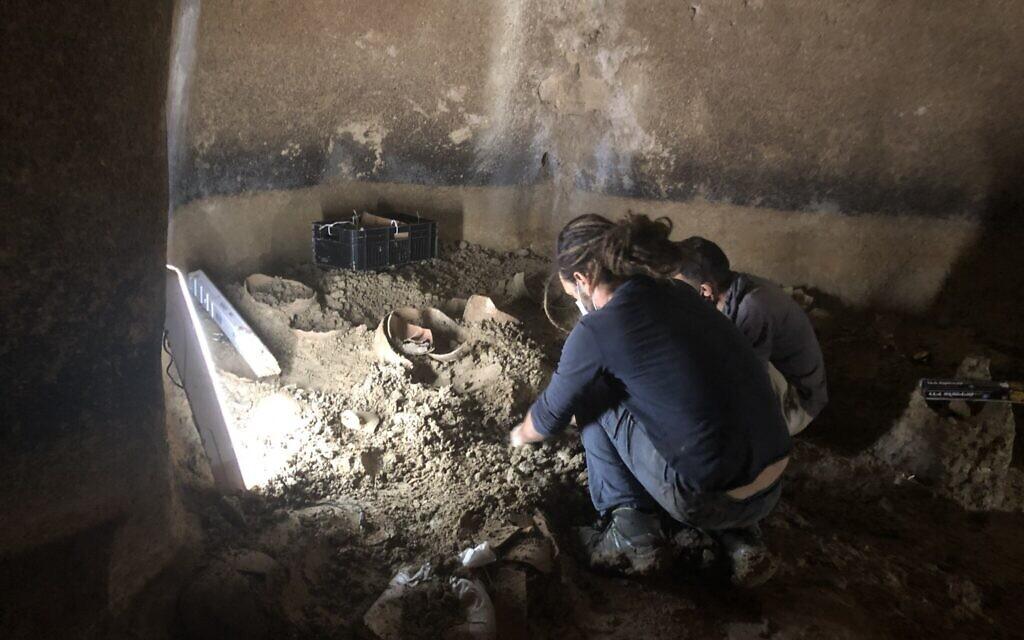 Un archéologue et un ouvrier retirent rapidement des récipients en poterie du fond d'une citerne d'eau datant de la période du Second Temple, dans l'ancien village de Kafr Murr, aujourd'hui un quartier de Beit El, le 3 novembre 2020. (Amanda Borschel-Dan/ToI)