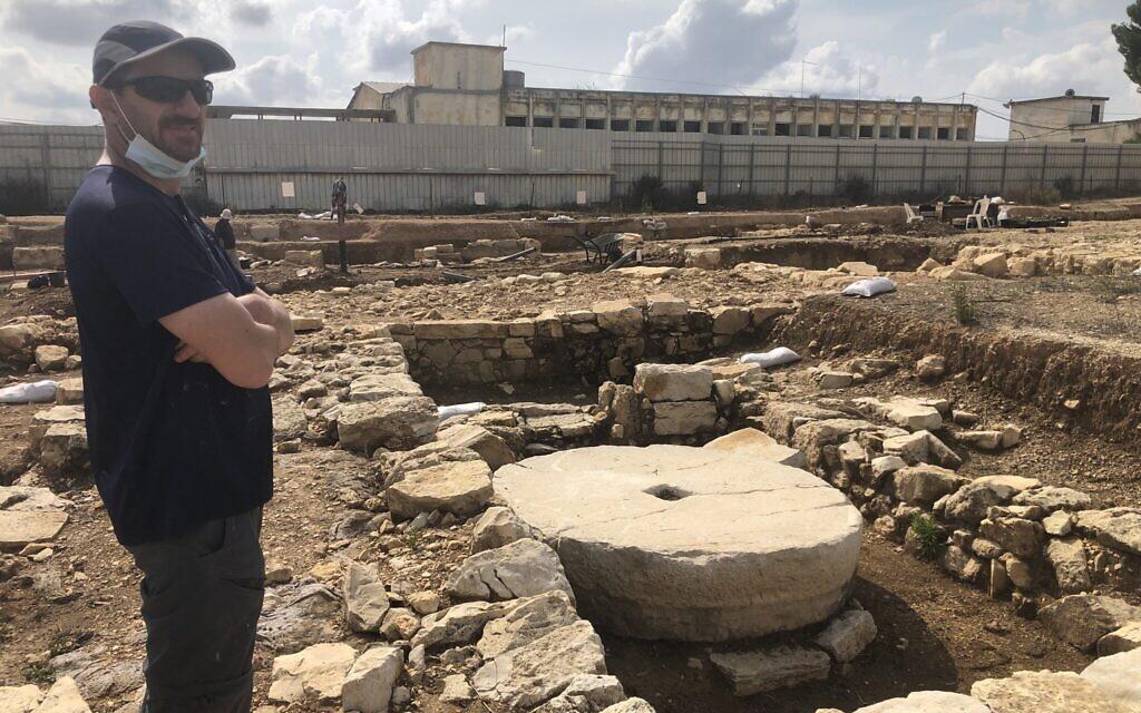 Le directeur des fouilles, Evgueni Aharonovitch, se tient à côté d'un pressoir à olives inutilisé de l'époque du Second Temple, dans l'ancien village de Kafr Murr, aujourd'hui un quartier de Beit El, le 3 novembre 2020. (Amanda Borschel-Dan/ToI)
