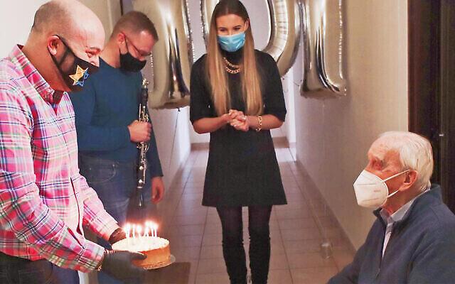 Jozef Walaszczyk, à droite, se voit offrir un gâteau pour son 101e anniversaire à Varsovie, en Pologne, le 12 novembre 2020. (Autorisation/From the Depths via JTA)