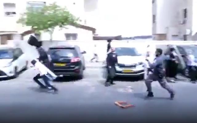 Un agent de police, à droite, jette un seau en direction d'un petit garçon lors d'une manifestation à Beitar Illit, le 4 octobre 2020. (Capture d'écran :  Twitter)