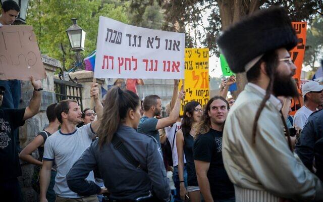 """Des manifestants laïcs israéliens scandent des slogans à Jérusalem  lors d'une manifestation de Juifs ultra-orthodoxes contre les commerces qui opèrent le samedi dans la ville, le 12 août 2017. Le slogan, qui rime en hébreu, dit : """"Nous ne sommes pas contre le sabbat, nous sommes contre la pression religieuse"""". (Crédit : Yonatan Sindel/Flash90 )"""