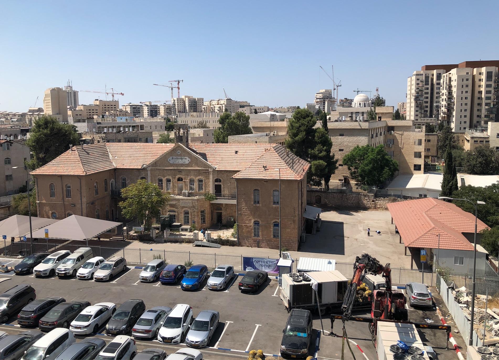 L'un des bâtiments du complexe Schneller, ancienne école pour aveugles, et qui est devenu une école religieuse pour filles et un parking municipal. (Crédit :  Jessica Steinberg/Times of Israel)
