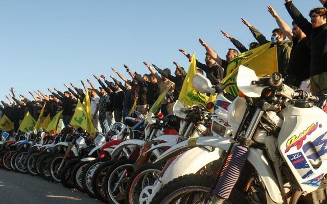 Des partisans du groupe terroriste libanais Hezbollah saluent à la façon des nazis alors qu'ils se tiennent derrière des motos portant les drapeaux du mouvement chiite dans le district de Marjayoun, au sud du Liban, à la frontière avec Israël, le 25 mai 2020. (Mahmoud Zayyat/AFP)