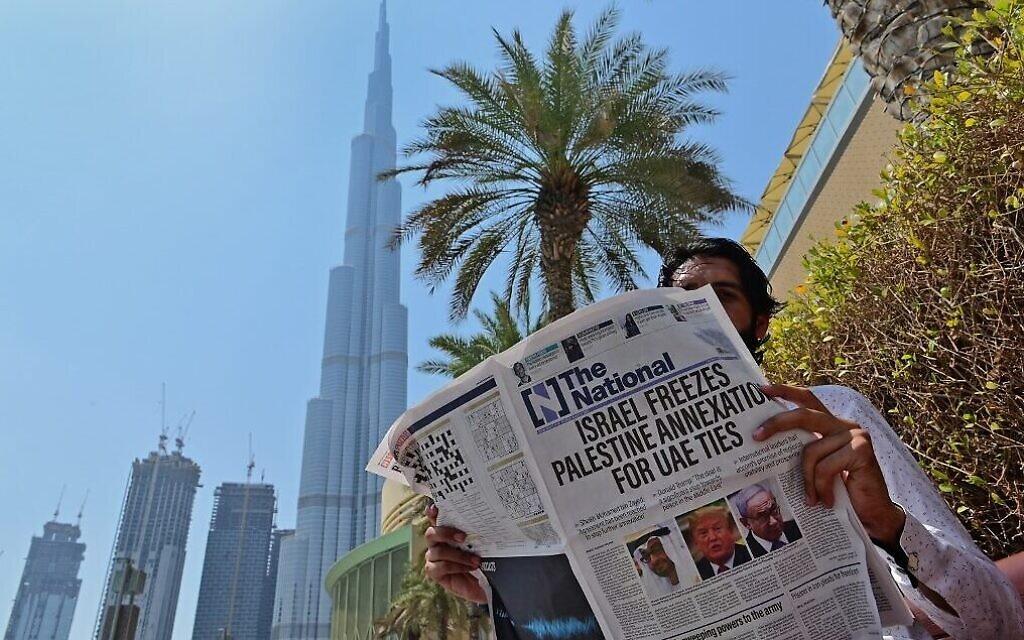 Un homme lit un exemplaire du journal émirati The National, avec en Une l'accord EAU-Israël et la suspension des mesures d'annexion par Israël, près du Burj Khalifa, la plus haute structure et le plus grand bâtiment du monde, à Dubaï le 14 août 2020. (Crédit : Giuseppe Cacace/AFP)