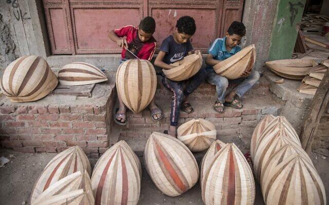 Des enfants travaillent sur des ouds en arabe dans un atelier appartenant à Khaled Azzouz, un oudiste chevronné, dans le quartier d'al-Marg, à la périphérie du Caire, la capitale égyptienne, le 26 octobre 2020. (Crédit : Khaled DESOUKI / AFP)
