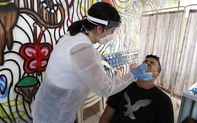 Une employée du centre médical Sheba utilise un écouvillon pour prélever un échantillon sur un étudiant pour un test de coronavirus au lycée hébraïque Herzliya à Tel Aviv, le 8 novembre 2020. (Jack Guez/ AFP)