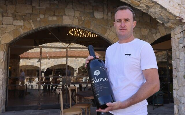 Le vigneron israélien Yaakov Berg tient une bouteille de son assemblage rouge nommé d'après le secrétaire d'État américain Mike Pompeo à la cave à vin de Psagot dans le parc industriel de Shaar Binyamin près de l'implantation israélienne de Psagot en Cisjordanie, au nord de Jérusalem, le 18 novembre 2020. (Emmanuel DUNAND / AFP)
