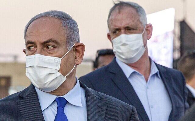 Le Premier ministre Benjamin Netanyahu (à gauche) et son partenaire de coalition, le ministre de la Défense Benny Gantz, tous deux masqués en raison de la pandémie de coronavirus COVID-19, arrivent pour assister à une cérémonie de remise de diplômes aux nouveaux pilotes sur la base aérienne d'Hatzerim près de Beer Sheva, le 25 juin 2020. (Ariel Schalit / POOL / AFP)