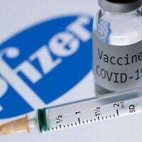 Photo d'illustration d'une seringue et d'un flacon contenant une dose de vaccin COVID-19 à côté du logo de la firme Pfizer, le 23 novembre 2020. (Crédit : JOEL SAGET / AFP)