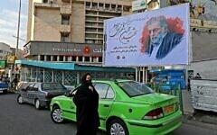 Une femme passe devant un panneau en hommage au scientifique nucléaire Mohsen Fakhrizadeh dans la capitale iranienne de Téhéran, le 30 novembre 2020. (Crédit : Atta Kenare/AFP)