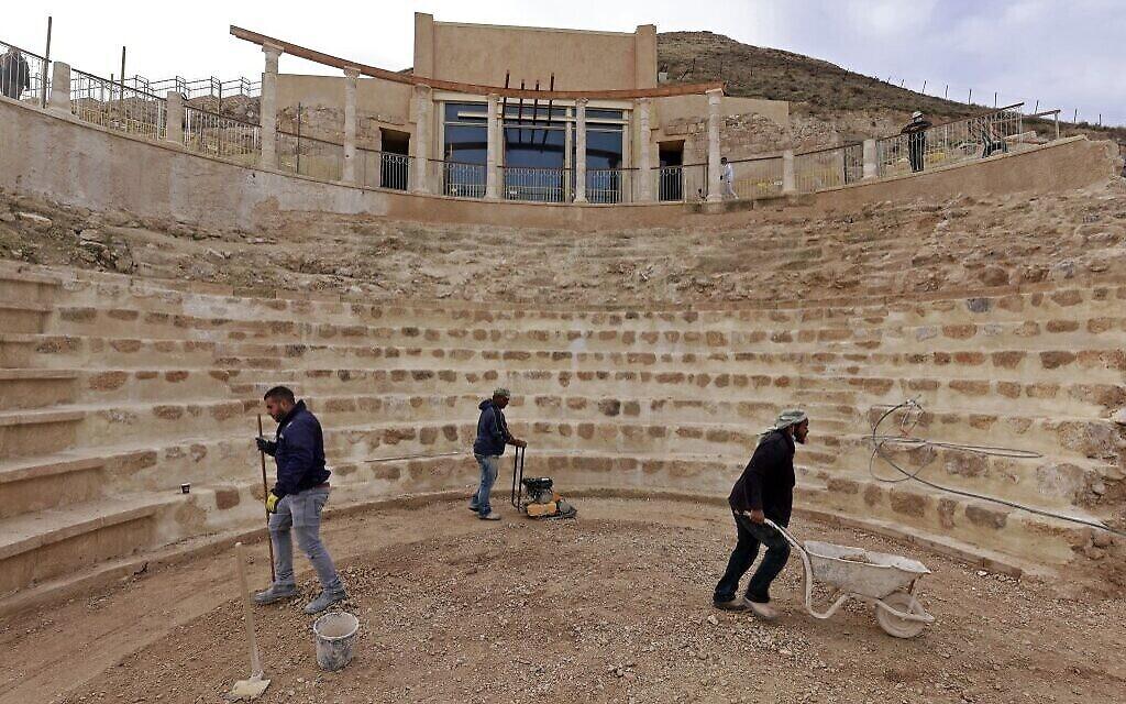 Des ouvriers aplanissent le sol restauré du théâtre antique construit par Hérode le Grand entre 23 et 15 avant l'ère commune dans le désert de Judée, au sud-est de Bethléem en Cisjordanie, le 7 décembre 2020. (Crédit : Menahem KAHANA / AFP)
