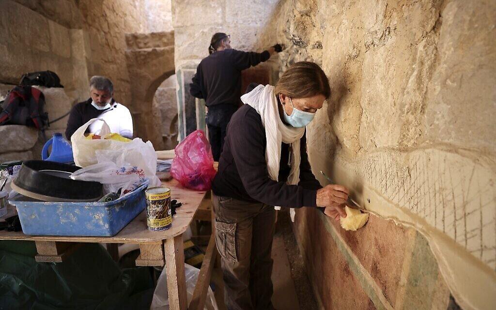 Une conservatrice de l'Autorité israélienne des antiquités restaure les fresques anciennes du couloir des arcs menant au palais d'Hérode le Grand construit par Hérode le Grand entre 23 et 15 avant l'ère commune dans le désert de Judée, au sud-est de Bethléem (Crédit : Menahem KAHANA / AFP)
