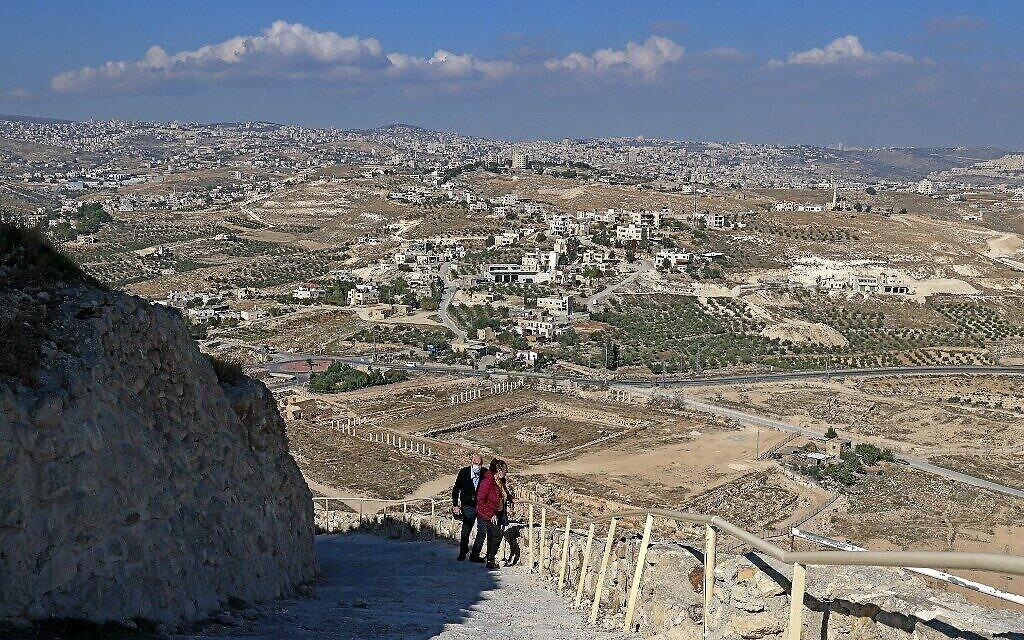 Un couple monte les marches menant à l'ancien palais d'Hérode le Grand construit par Hérode le Grand entre 23 et 15 avant l'ère commune, dans le désert de Judée, au sud-est de Bethléem, le 24 novembre 2020. (Crédit : Menahem KAHANA / AFP)