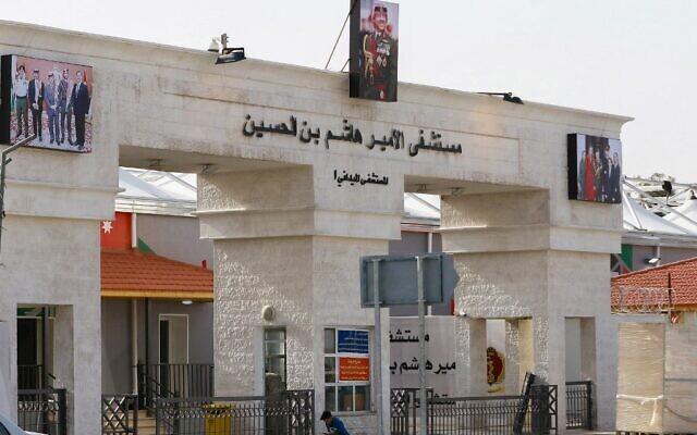 Un petit garçon assis devant l'entrée principale de l'hôpital de campagne  Prince Hashem bin Hussein, premier hôpital consacré à la Covid-19 dans le pays, à Zarqa, à 25 kilomètres de la capitale Amman, le 8 décembre 2020. (Crédit :  Khalil MAZRAAWI / AFP)