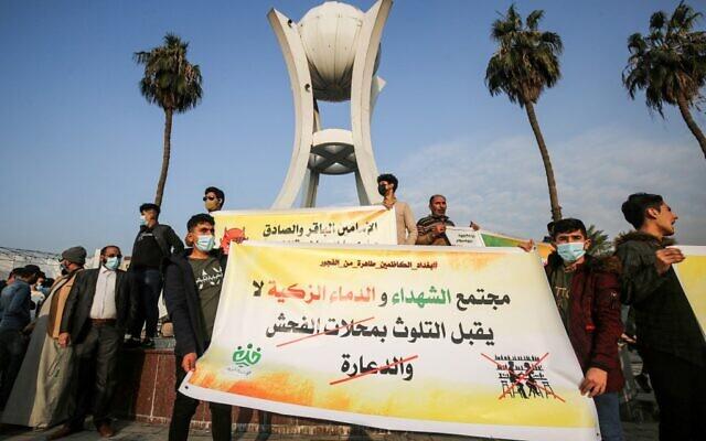 """Des jeunes d'un groupe se faisant appeler """"Tajammu' Shabab al-Sharia"""" (Rassemblement des jeunes pour la Sharia) brandissent une banderole condamnant les magasins d'alcool et les maisons closes lors d'une manifestation à Bagdad, la capitale irakienne, le 3 décembre 2020, pour exiger la fermeture des boîtes de nuit et des ventes de boissons alcoolisées. (Crédit : AHMAD AL-RUBAYE / AFP)"""