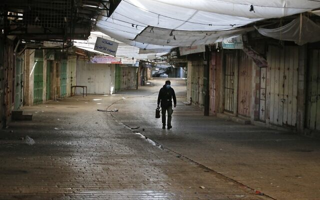 Un vendeur de café de rue marche parmi des boutiques fermées dans le contexte de la pandémie de COVID-19 en Cisjordanie, à Hébron, le 11 décembre 2020. (Crédit :  HAZEM BADER / AFP)