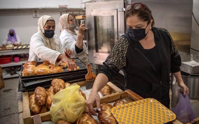 """Une femme juive marocaine remplit des sacs de pâtisseries pour servir les clients de la boulangerie casher """"Madame Fhal"""" dans la ville portuaire de Casablanca, le 11 décembre 2020. (Crédit : FADEL SENNA / AFP)"""