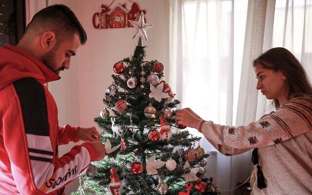 Saad Polus Qiryaqoz, un réfugié chrétien de 56 ans de la ville de Bartella, dans la plaine de Ninive au nord de l'Irak, décore un arbre de Noël dans sa nouvelle maison à Amman, la capitale jordanienne, le 18 décembre 2020. (Crédit : Khalil MAZRAAWI / AFP)