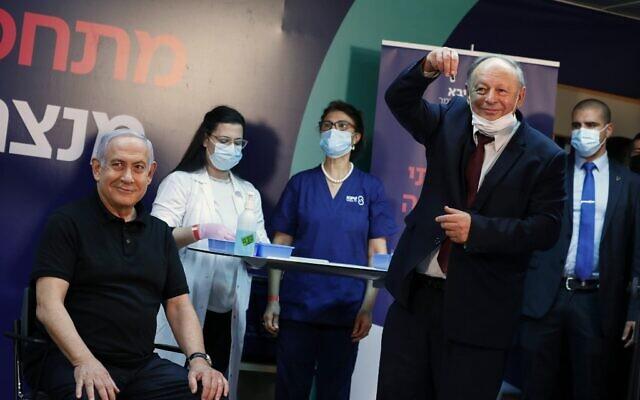 Le Premier ministre Benjamin Netanyahu , 71 ans, sourit avant d'être vacciné contre le coronavirus. (Crédit : AMIR COHEN / POOL / AFP)