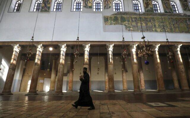 Un prêtre orthodoxe se promène dans l'église de la Nativité, dans la ville de Bethléem en Cisjordanie, le 20 décembre 2020. (Crédit : HAZEM BADER / AFP)