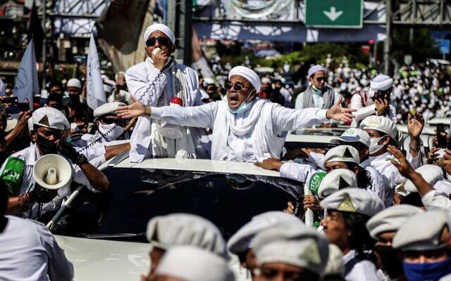Le leader musulman Rizieq Shihab, chef de l'organisation indonésienne radicale du Front des défenseurs de l'islam, alpague ses partisans lors de l'inauguration d'une mosquée à Bogor, le 13 novembre 2020. (Crédit : ADITYA SAPUTRA / AFP)