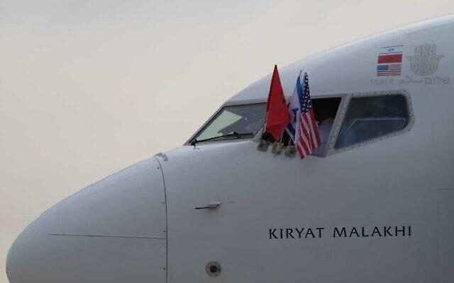 Les drapeaux nationaux du Maroc, d'Israël et des États-Unis à la fenêtre du cockpit d'un avion El Al à destination du Maroc, avec à son bord la délégation en charge de finaliser l'accord de normalisation entre Jérusalem et Rabat, à l'aéroport Ben Gourion, près de Tel Aviv, le 22 décembre 2020. (Crédit : Judah Ari Gross / Times of Israel)