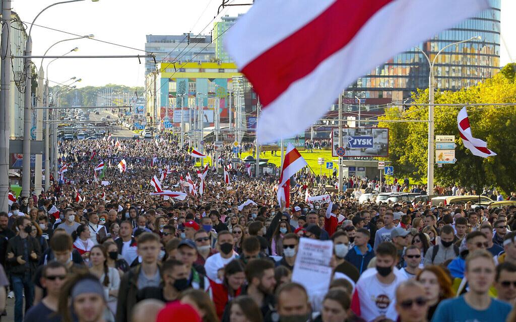 Des manifestants brandissent le vieux drapeau national biélorusse pendant un rassemblement de l'opposition pour protester contre les résultats officiels des élections présidentielles à Minsk, en Biélorussie, le 20 septembre 2020. (Crédit :  AP Photo/TUT.by)