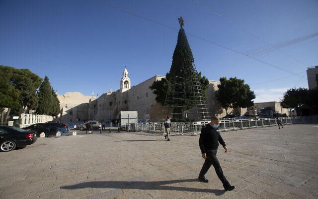 Un homme marche devant l'église de la Nativité, traditionnellement considérée comme le lieu de naissance de Jésus-Christ, dans la ville de Bethléem, en Cisjordanie, le 23 novembre 2020. (Crédit : AP / Majdi Mohammed)