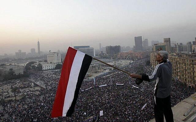Un Égyptien agite un drapeau national au-dessus d'un rassemblement pro-militaire marquant le troisième anniversaire du soulèvement de 2011 sur la place Tahrir au Caire, en Égypte, le samedi 25 janvier 2014. (Crédit : AP/Amr Nabil)