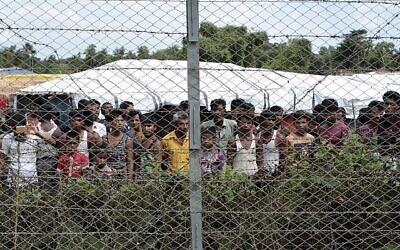 Sur cette photo du 29 juin 2018, des réfugiés rohingyas se rassemblent près d'une clôture lors d'une tournée médiatique organisée par le gouvernement, dans le no man's land entre le Myanmar et le Bangladesh, près du village de Taungpyolatyar, Maung Daw, dans le nord de l'État de Rakhine, au Myanmar. (Photo AP / Min Kyi Thein)