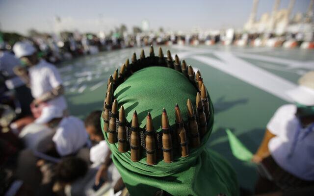 Un partisan des rebelles chiites Houthis, avec une ceinture de munitions placée sur sa tête, assiste à une célébration à Sanaa, au Yémen, le 9 novembre 2019. (Crédit : Hani Mohammed/AP)