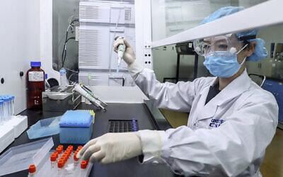Une scientifique teste des échantillons d'un potentiel vaccin contre la COVID-19 dans une usine de production de SinoPharm, à Pékin, le 11 avril 2020. Dans sa course mondiale à la fabrication d'un vaccin contre le coronavirus, l'entreprise publique chinoise se vante d'avoir donné à ses employés, y compris ses hauts dirigeants, des injections expérimentales avant même que le gouvernement n'accepte de le tester sur des citoyens. (Crédit : Zhang Yuwei / Xinhua via AP)