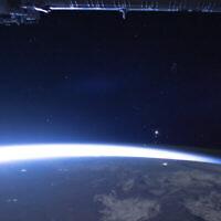 Sur cette image diffusée par la NASA, la comète Neowise, à gauche, apparaît à l'est, au dessus de la terre, une image prise par la Station spatiale internationale, le 5 juillet 2020. (Crédit : NASA via AP)