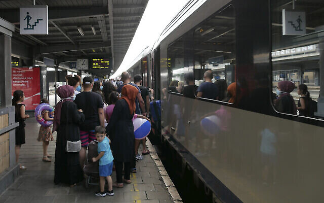 Illustration : des gens attendent de monter à bord d'un train à Bruxelles pour la station balnéaire belge de Blankenberge, en Belgique, le 11 août 2020. (AP Photo / Sylvain Plazy)