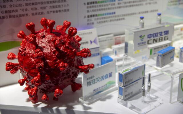 Un modèle du coronavirus à côté de boîtes pour les vaccins contre la COVID-19 lors d'une exposition de la société pharmaceutique chinoise SinoPharm au Salon international chinois du commerce des services (CIFTIS) à Pékin, le 5 septembre 2020. (Crédit : Mark Schiefelbein / AP)