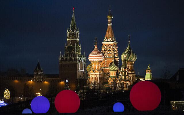 La cathédrale Saint-Basile, à droite, et la tour Spasskaya du Kremlin sont éclairées derrières les boules lumineuses installées pour la célébration du Nouvel An et de Noël dans le parc Zaryadye à Moscou, Russie, le 23 décembre 2020. (Crédit : Pavel Golovkin / AP)