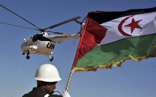Un soldat tient un drapeau sahraoui alors qu'un hélicoptère des Nations unies survole le camp de réfugiés de Smara près de Tindouf, dans le sud-ouest de l'Algérie, le 5 mars 2016. (Crédit : AP Photo/Toufik Doudou)