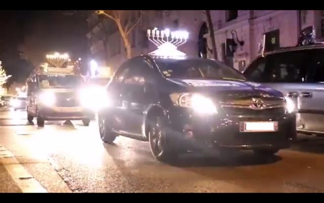 Capture d'écran d'une vidéo du site Hassidout.org publiée le 13 décembre 2020 montrant des voitures surmontées d'une Hanoukkia, diffusant de la musique et défilant dans les rues de Paris. (Crédit : Hassidout.org)