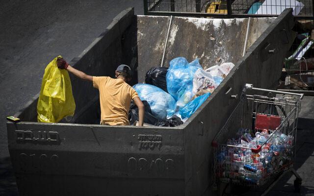 Un adolescent cherche des boîtes dans un conteneur à poubelles dans le centre de Jérusalem, le 13 juillet 2020. (Crédit : Olivier Fitoussi/Flash90)