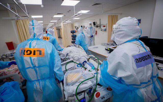 Des membres du personnel médical hospitalier portant des vêtements de protection transfèrent des patients dans un service de traitement du coronavirus au centre médical Shaare Zedek à Jérusalem, le 16 novembre 2020. (Olivier Fitoussi/Flash90)