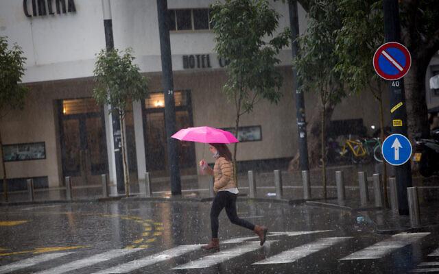 Une femme munie d'un parapluie par une journée pluvieuse d'hiver à Tel-Aviv, le 16 décembre 2020. (Crédit : Miriam Alster/Flash90)