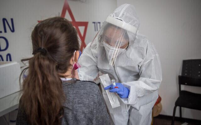 Un travailleur médical du Magen David Adom teste une Israélienne pour le coronavirus sur un site de tests mobile à Jérusalem le 16 décembre 2020. (Crédit : Yonatan Sindel / Flash90)