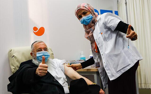 Un citoyen israélien se fait vacciner contre la COVID-19 dans un centre de vaccination de la Meuhedet à Jérusalem, le 21 décembre 2020. (Crédit : Olivier Fitoussi/Flash90)