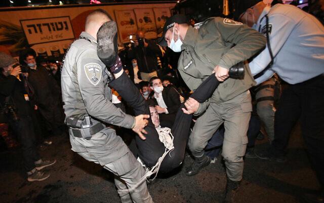 Des affrontements entre la police et des Juifs ultra-orthodoxes qui protestent contre l'arrestation d'un étudiant, dans la ville centrale de Bnei Brak, le 27 décembre 2020. (Crédit : Noam Revkin Fenton / Flash90)