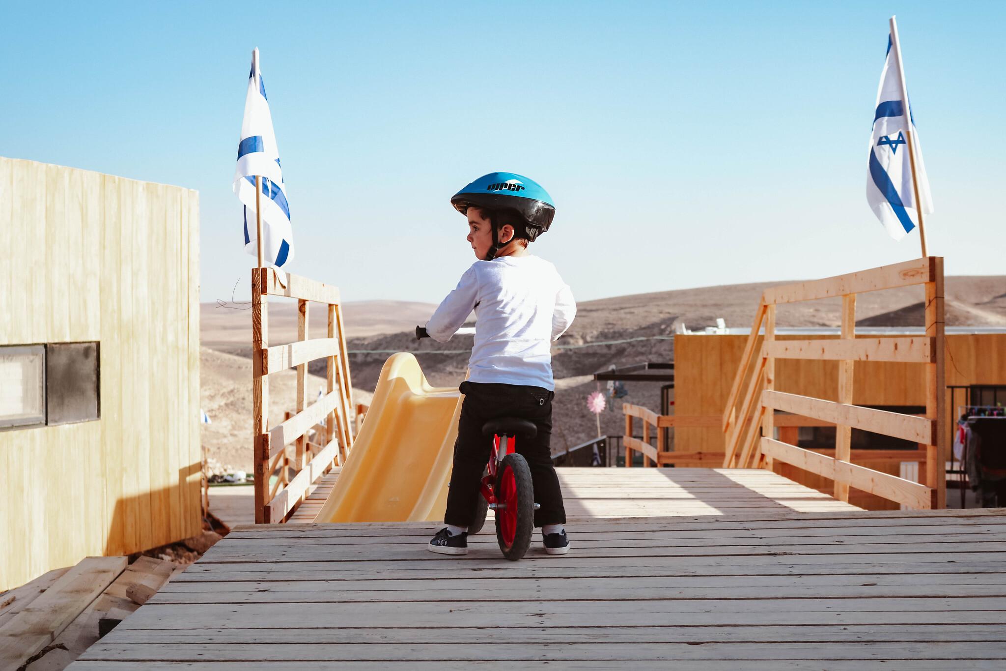 Un enfant sur un vélo  dans le quartier temporaire de Shahak Heights à Dimona, dans le sud d'Israël, le21 décembre 2020. (Crédit : Sue Surkes/Times of Israel)