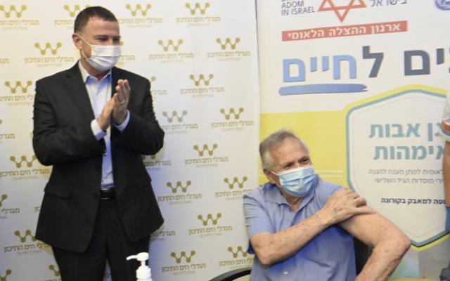 Yuli Edelstein applaudit alors qu'un homme est vacciné dans un centre de soins pour personnes âgées à Shaarei Tikva, le 22 décembre 2020. (Ministère de la Santé)