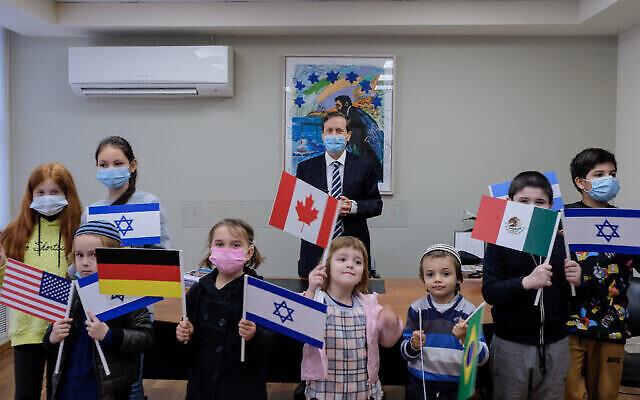 Le président de l'Agence juive Isaac Herzog, au centre, rencontre des enfants qui ont immigré en Israël pendant la pandémie de coronavirus, 28 décembre 2020. (David Salem / Agence juive pour Israël)